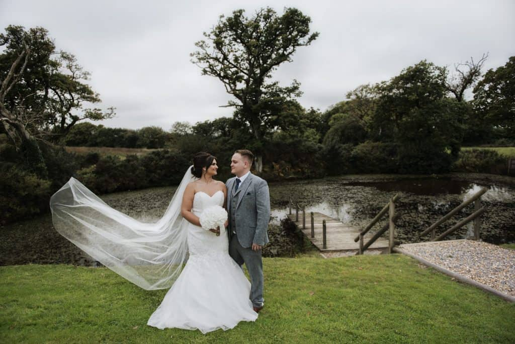 Bride & groom stood on grass in front of lake Oldwalls Wedding Photographer