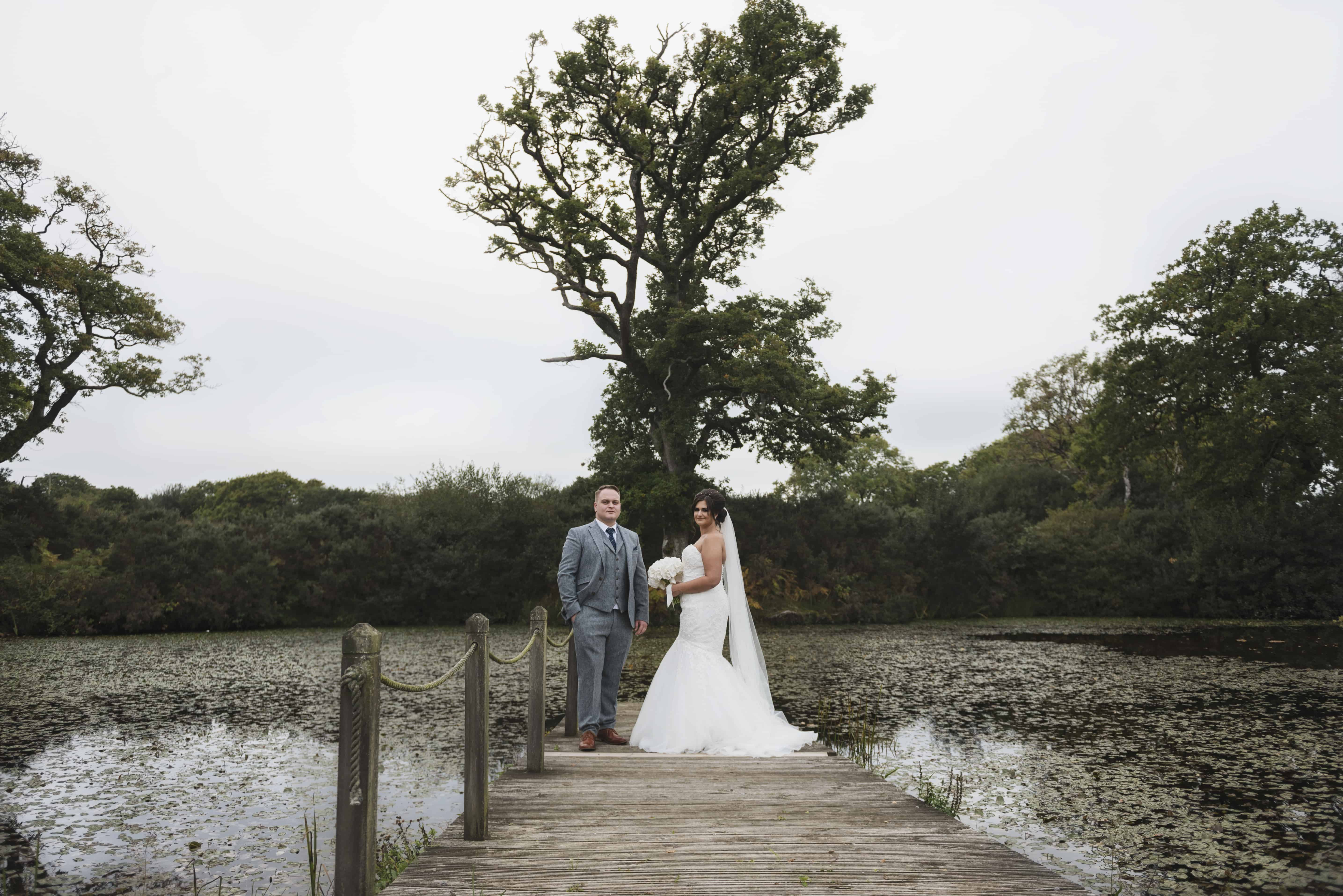 Bride & groom stood jetty in front of lake Oldwalls Wedding Photographer