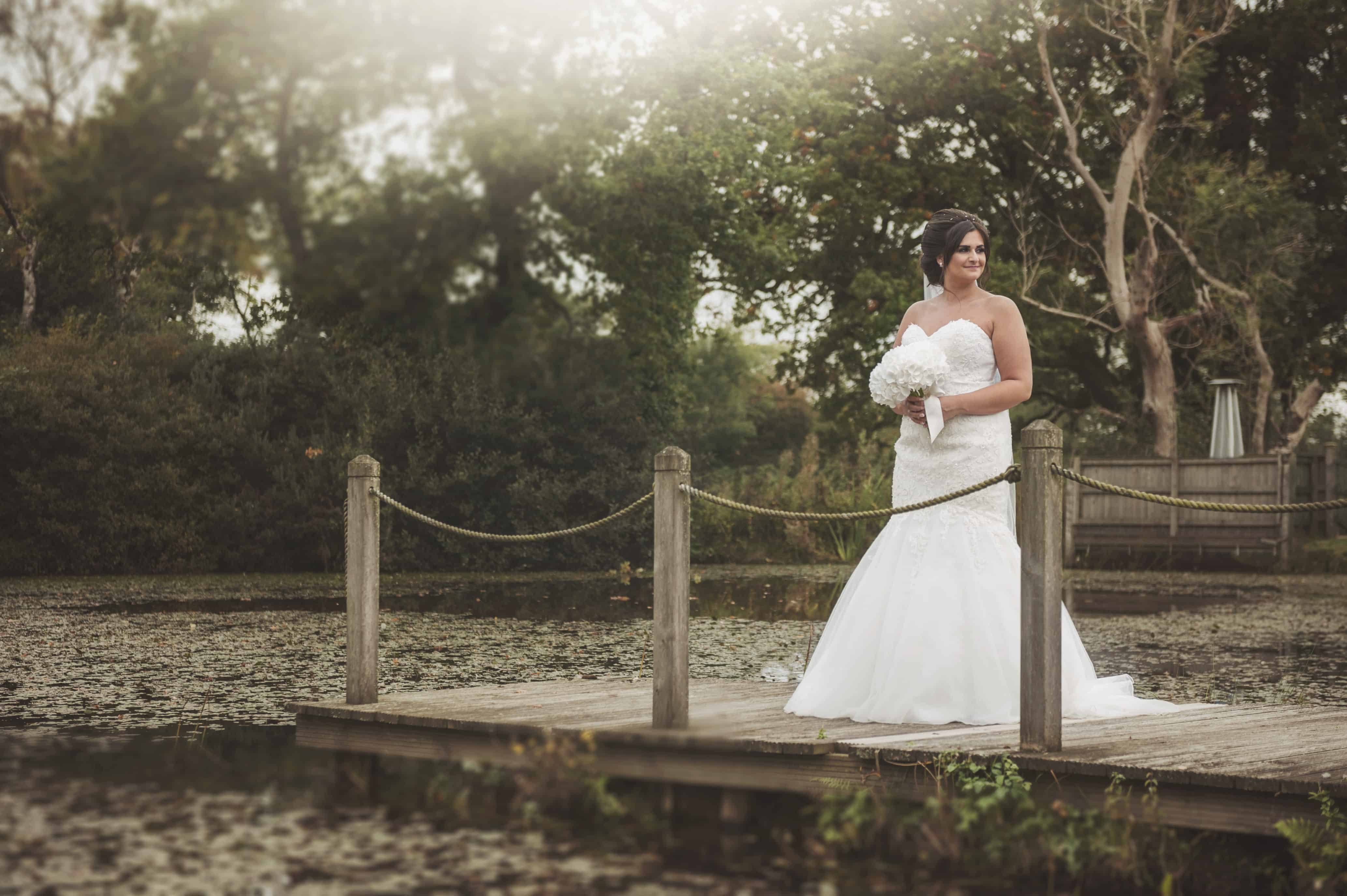 Bride stood on jetty in front of lake Oldwalls Wedding Photographer