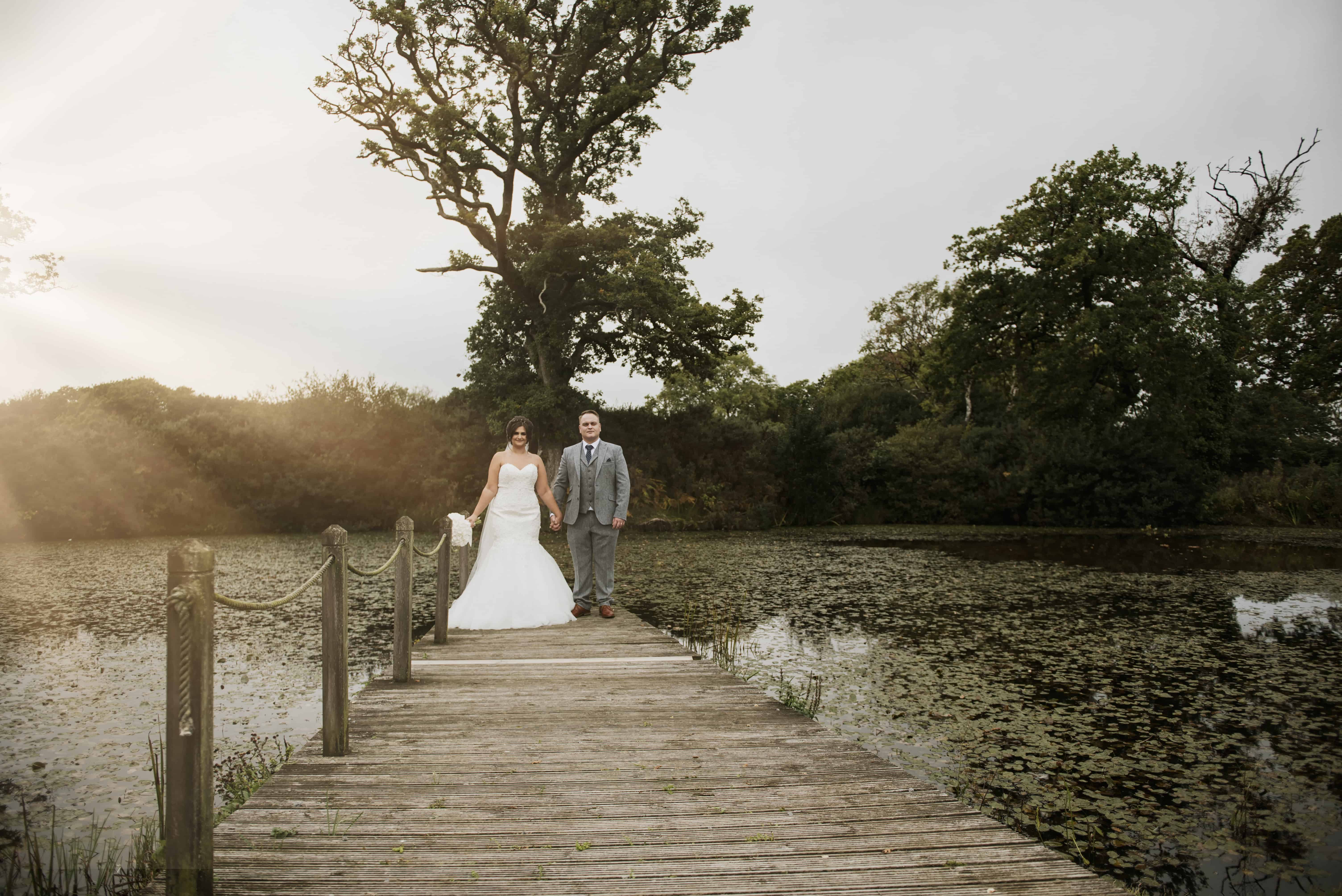Bride & groom stood on jetty in front of lake Oldwalls Wedding Photographer