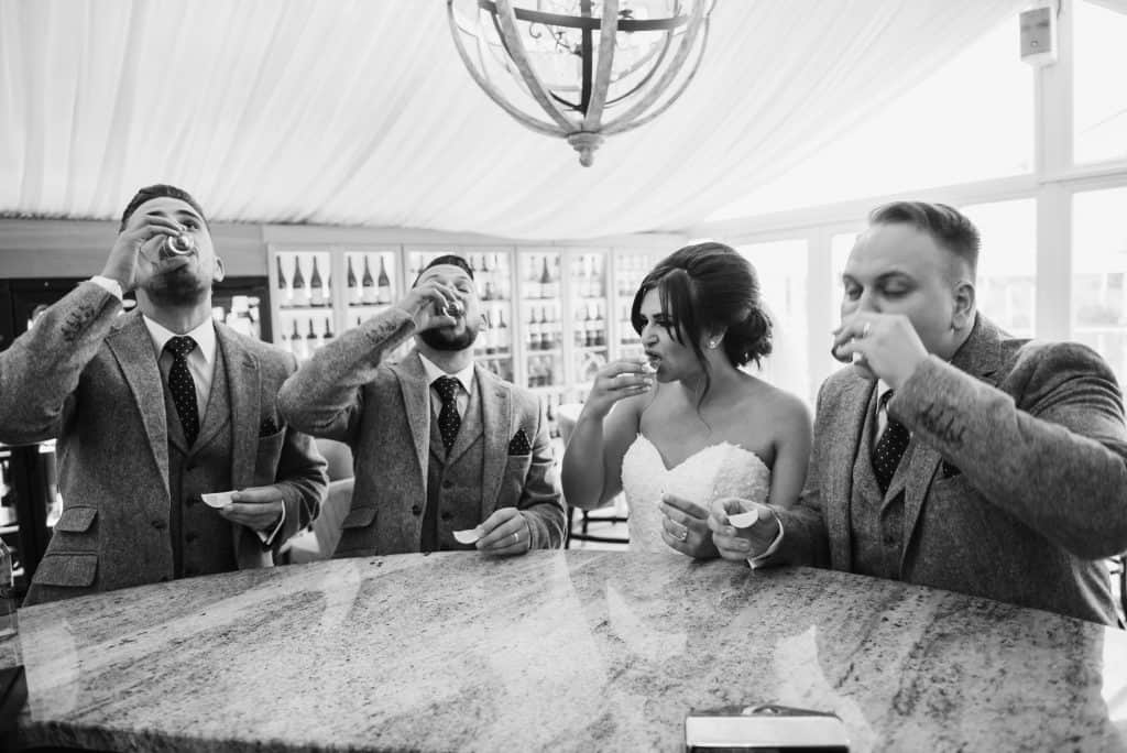 Bride groom and best men stood at bar doing shots Oldwalls Wedding Photographer