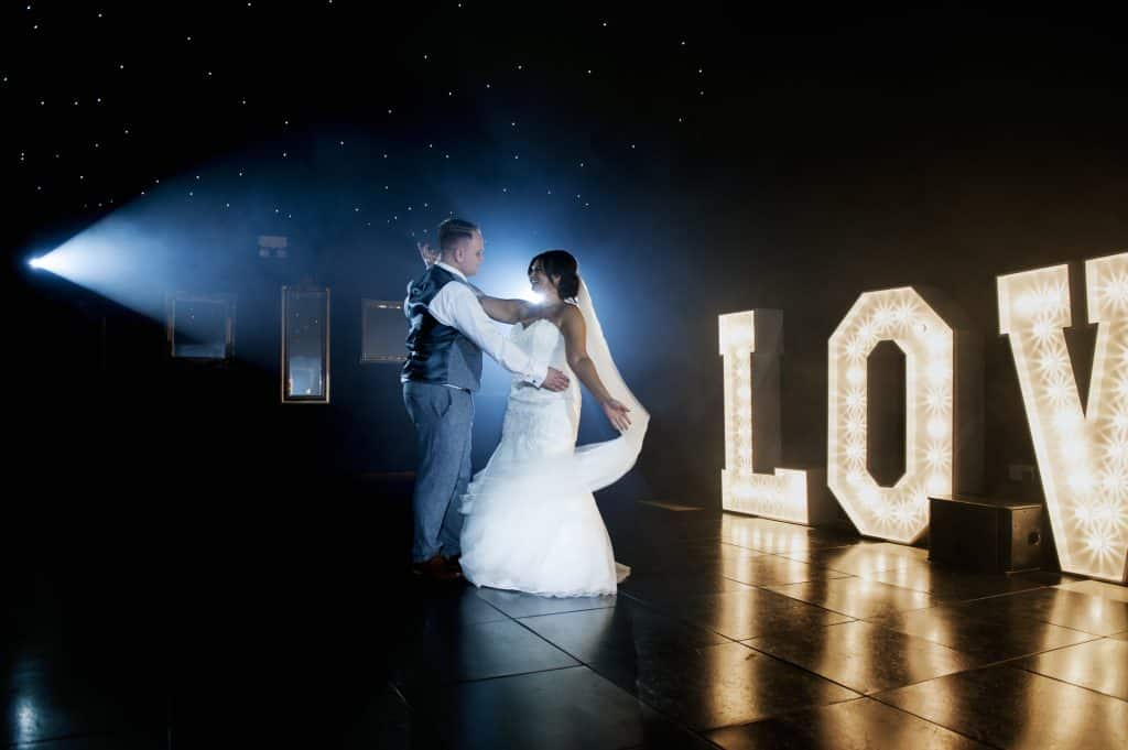 Bride & Groom dancing their first dance in front of illuminated love sign Oldwalls Wedding Photographer