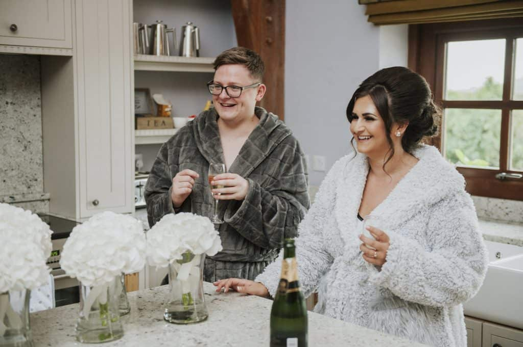 Man & woman in dressing gowns drinking champagne Oldwalls Wedding Photographer