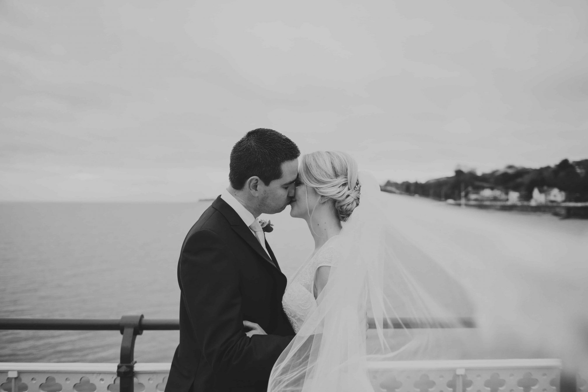 Best Wedding Photographer South Wales Bride and Groom stood on pier kissing