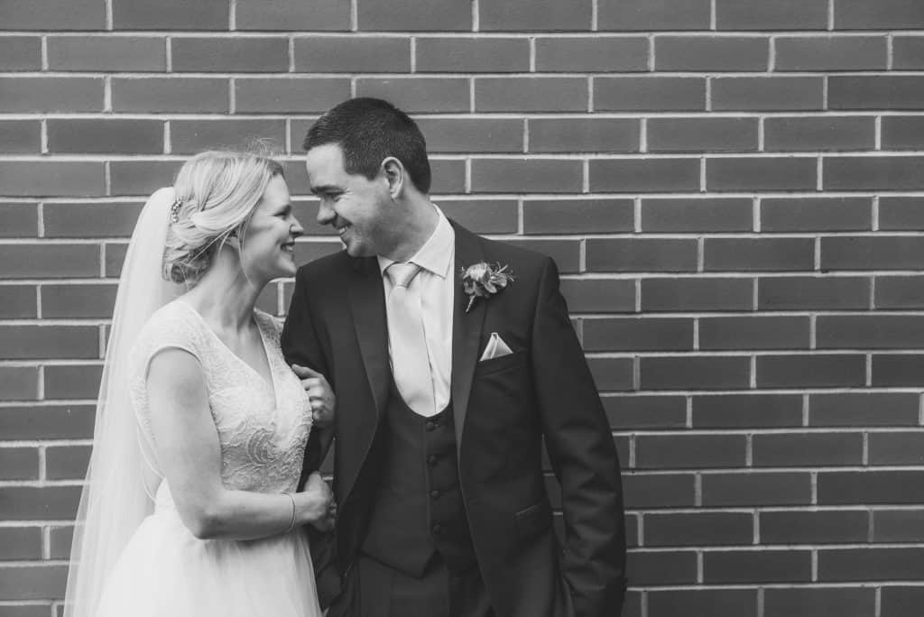 Holm House Wedding - Bride & Groom Stood in front of a brick wall laughing together