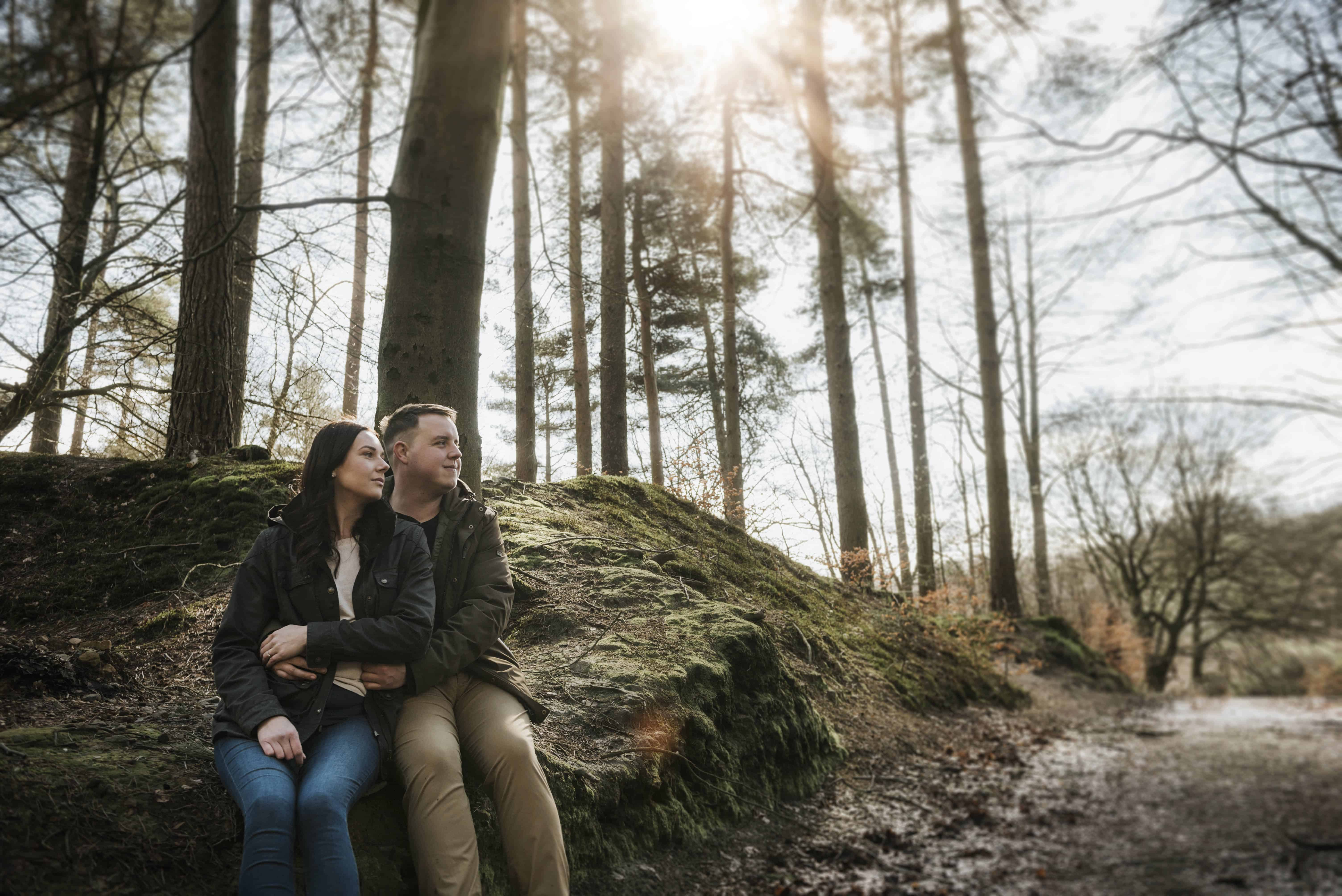 blaen bran community walk - Couple sat on tree stump with sun shining
